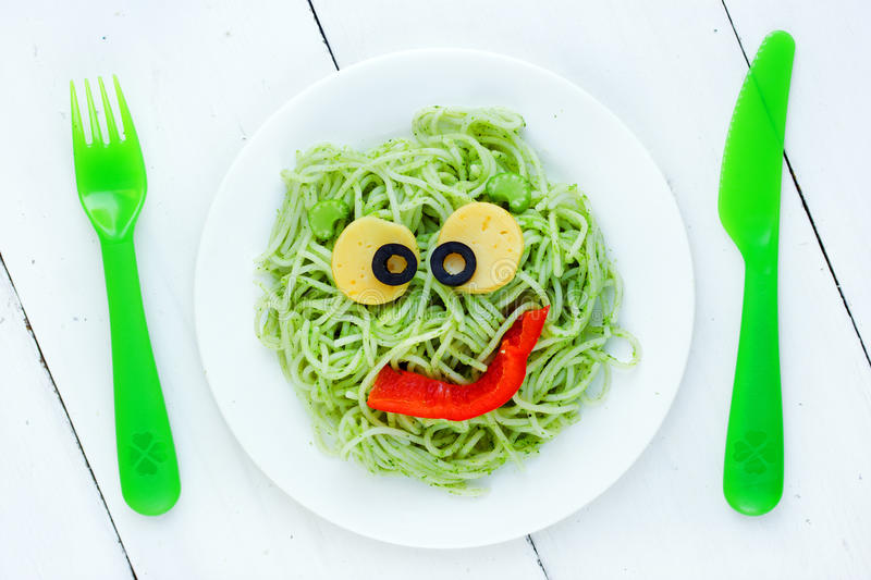 Healthy and creative kids lunch - green spaghetti pasta smiling. Funny crazy monster top view stock image