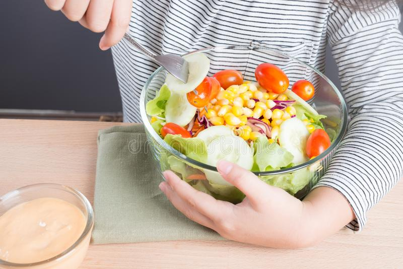 Healthy cute little asian girl hand hold salad bowl and eat salad stock photography