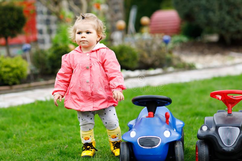Healthy cute little baby girl playing with two toy cars in garden. Adorable toddler child having fun. Girl in colorful. Fashion clothes. Spring and summertime royalty free stock photo