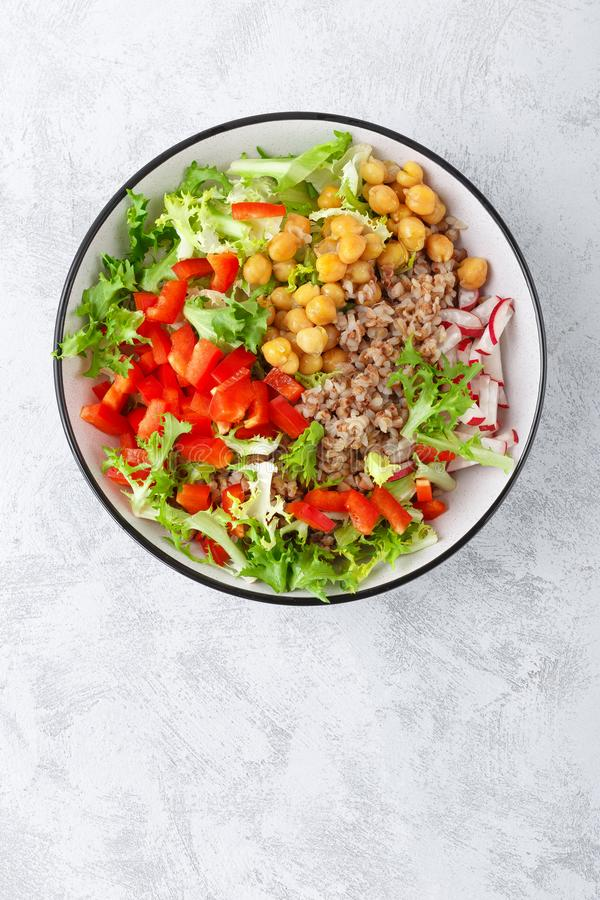 Healthy and delicious bowl with buckwheat and salad of chickpea, fresh pepper and lettuce leaves. Dietary balanced plant-based foo royalty free stock photography