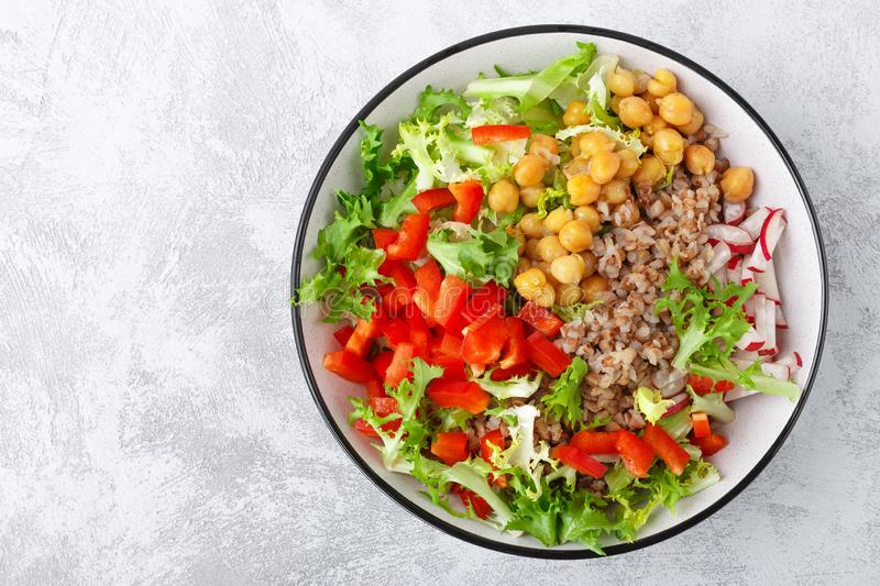 Healthy and delicious bowl with buckwheat and salad of chickpea, fresh pepper and lettuce leaves. Dietary balanced plant-based foo stock image