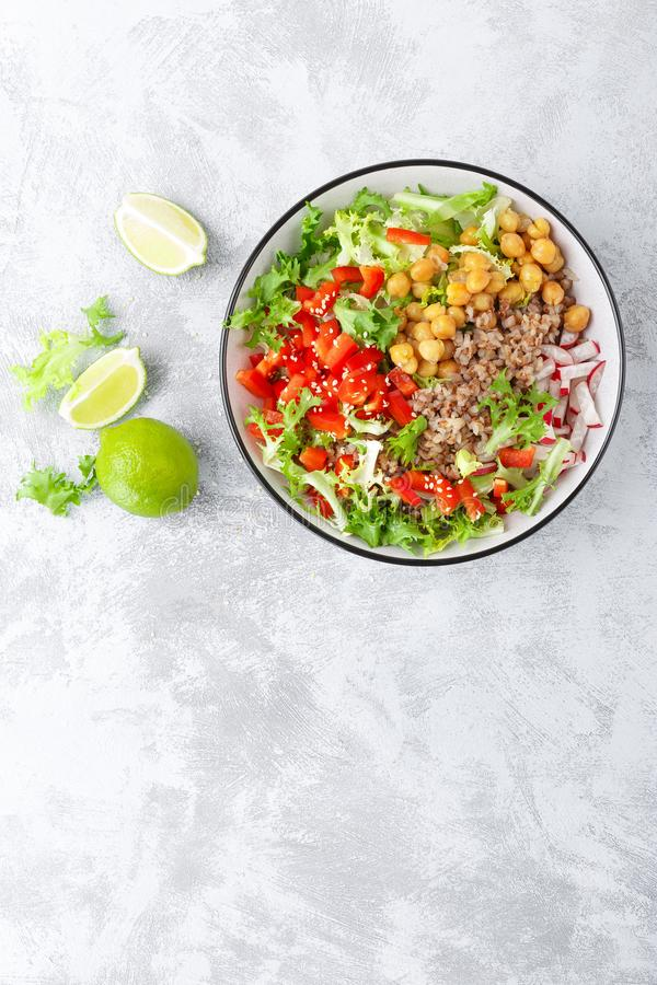 Healthy and delicious bowl with buckwheat and salad of chickpea, fresh pepper and lettuce leaves. Dietary balanced plant-based foo stock photography