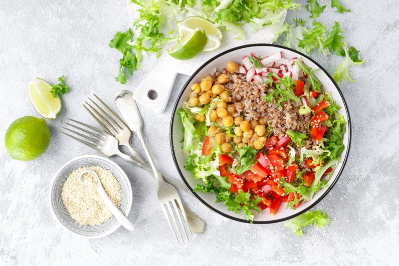 Healthy and delicious bowl with buckwheat and salad of chickpea, fresh pepper and lettuce leaves. Dietary balanced plant-based foo royalty free stock image