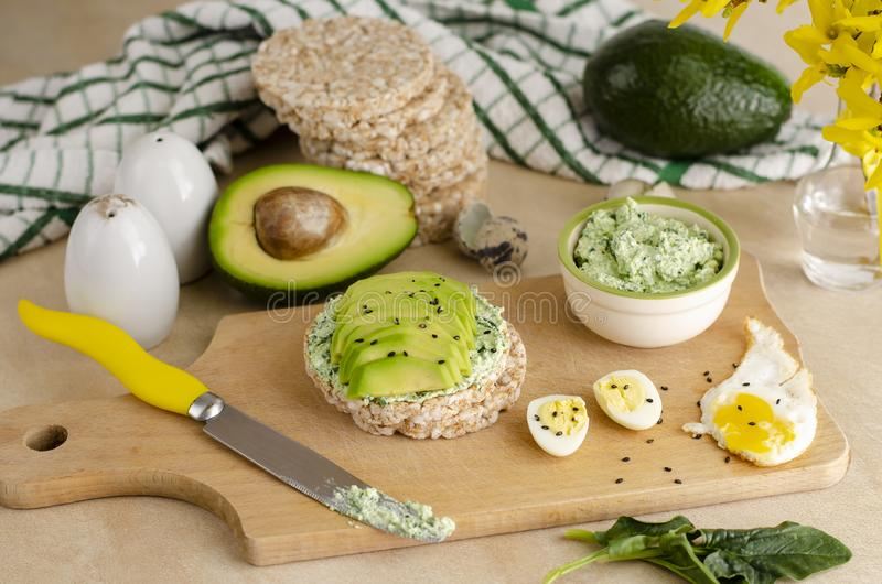 Healthy delicious breakfast or lunch. Buckwheat crispbread with cottage cheese, spinach and avocado. Healthy food and ketogenic diet concept stock photography