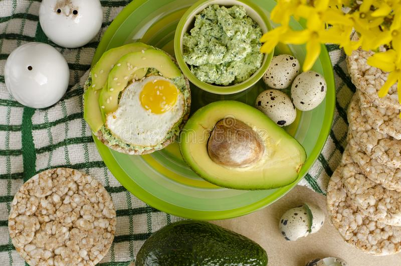 Healthy delicious breakfast or lunch. Buckwheat crispbread with cottage cheese, spinach, avocado and fried quail egg on a green plate. Healthy delicious stock photos
