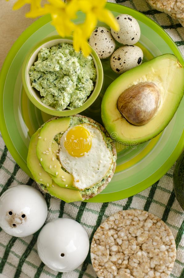 Healthy delicious breakfast or lunch. Buckwheat crispbread with cottage cheese, spinach, avocado and fried quail egg on a green plate. Healthy delicious royalty free stock photo