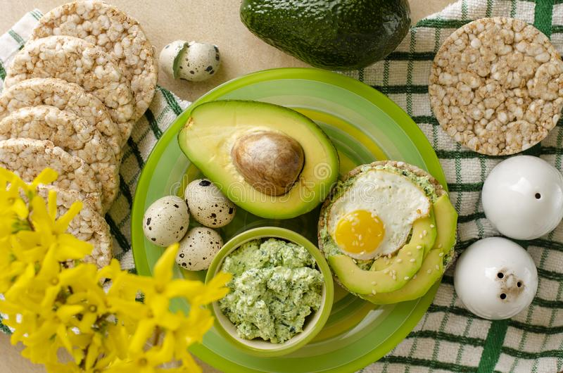Healthy delicious breakfast or lunch. Buckwheat crispbread with cottage cheese, spinach, avocado and fried quail egg on a green plate. Healthy delicious stock photo