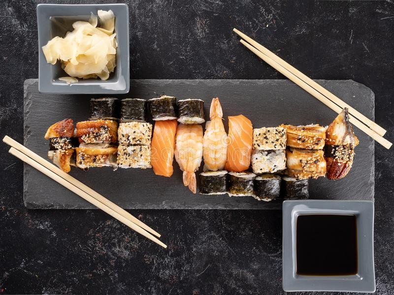 Healthy and delicious variety of sushi on dark stone royalty free stock photos