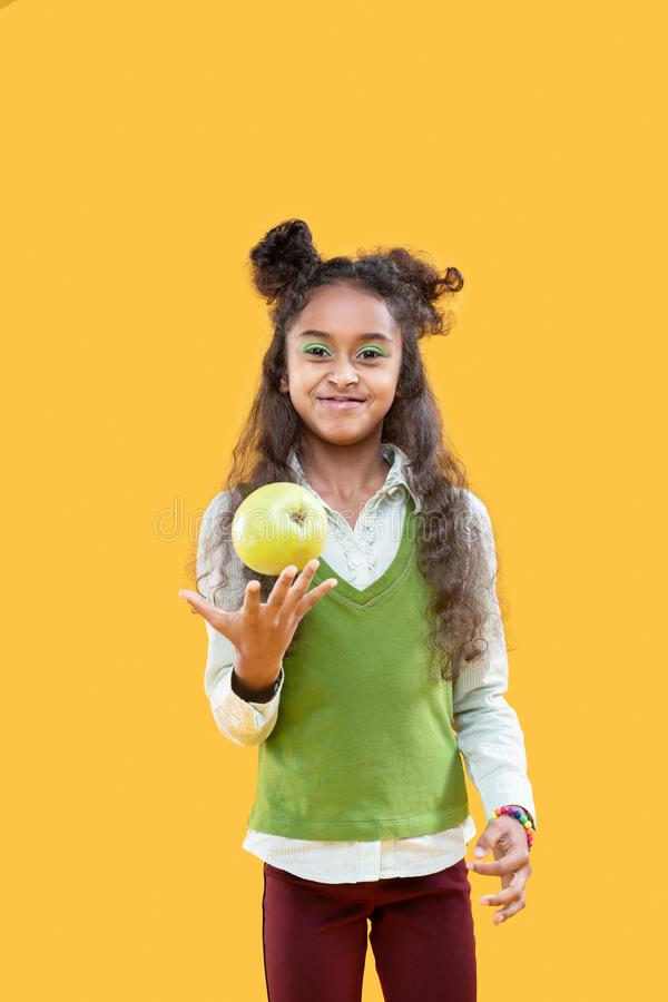 Delighted happy girl holding a green apple royalty free stock photos