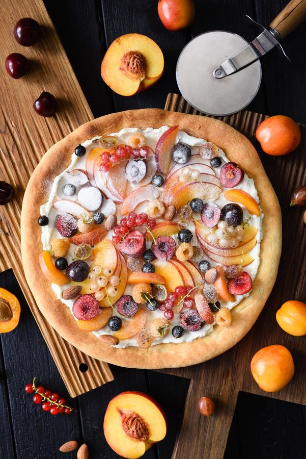 Healthy dessert. Flatlay of fruit sweet pizza made with peaches, apricots, cherries, currants and ricotta cream on dark wooden. Background overhead view royalty free stock photography