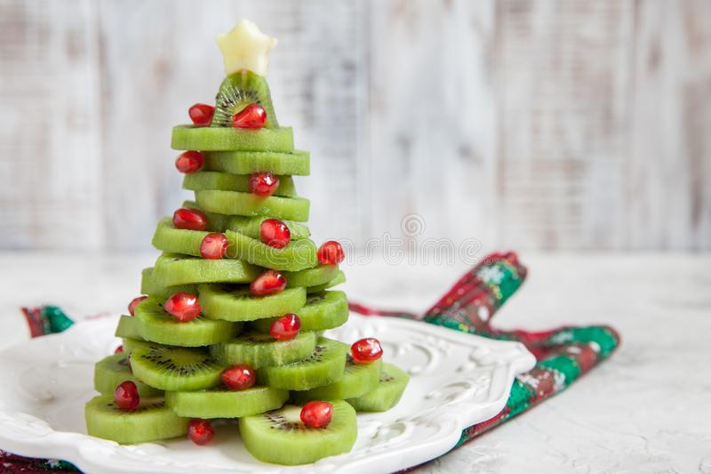 Healthy dessert idea for kids party - funny edible kiwi pomegranate Christmas tree. Beautiful New Year background stock images