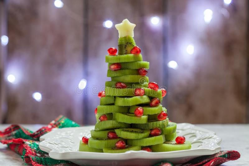 Healthy dessert idea for kids party - funny edible kiwi pomegranate Christmas tree. Beautiful New Year background royalty free stock photo