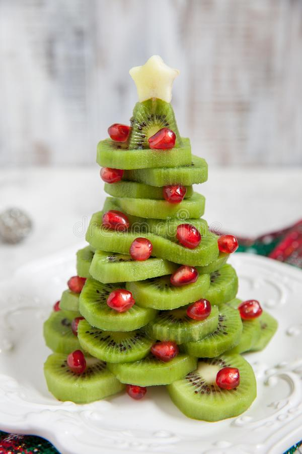 Healthy dessert idea for kids party - funny edible kiwi pomegranate Christmas tree. Beautiful New Year background stock photos