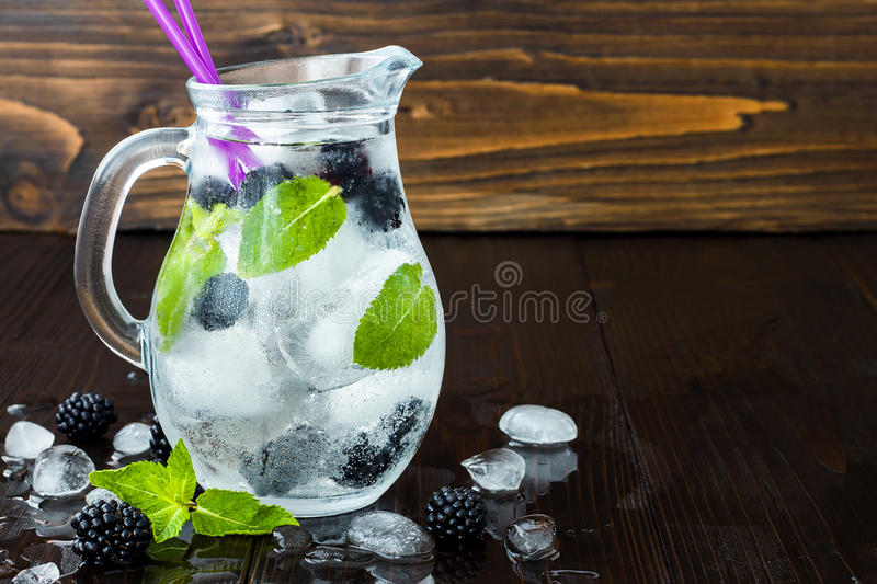 Healthy detox flavored water with blackberry and mint. Cold refreshing berry drink with ice on dark wooden table. Copy space backg. Round royalty free stock photo