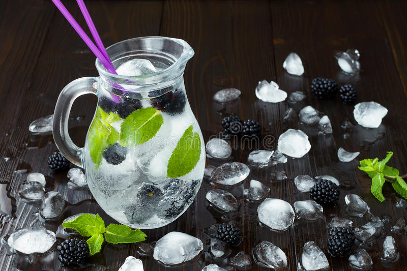 Healthy detox flavored water with blackberry and mint. Cold refreshing berry drink with ice on dark wooden table. Copy space backg. Healthy detox flavored water stock images