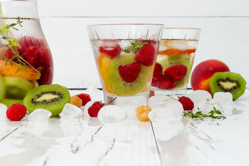 Healthy detox fruit infused flavored water. Summer refreshing homemade cocktail with fruits, thyme on wooden table. Clean eating royalty free stock image