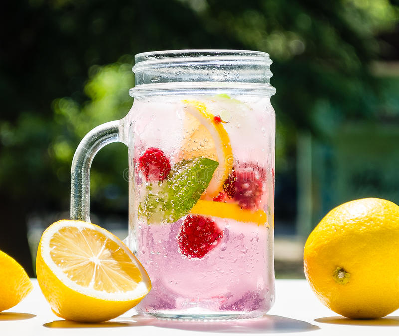 Healthy detox water served in a mason jar with ice lemon raspberries mint leaf bubbles and surrounded with green nature and trees stock photography