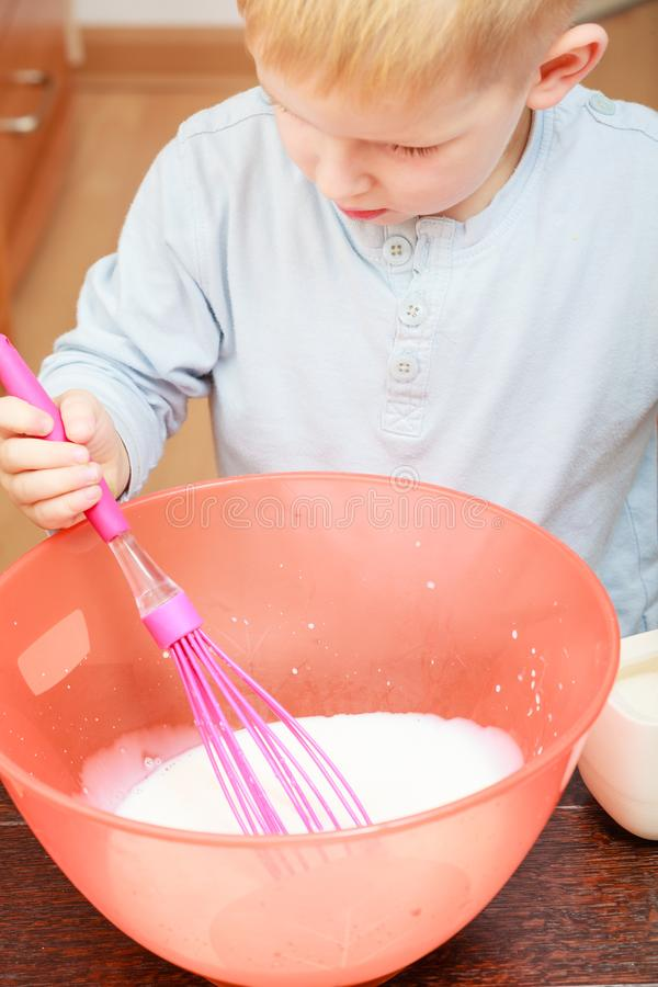 Little kid boy cooking, making cake in bowl stock photo