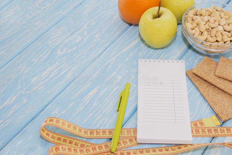 Healthy diet, fitness and weight loss concept, apple, notepad, pencil, measuring tape on the table. View from above. stock photos