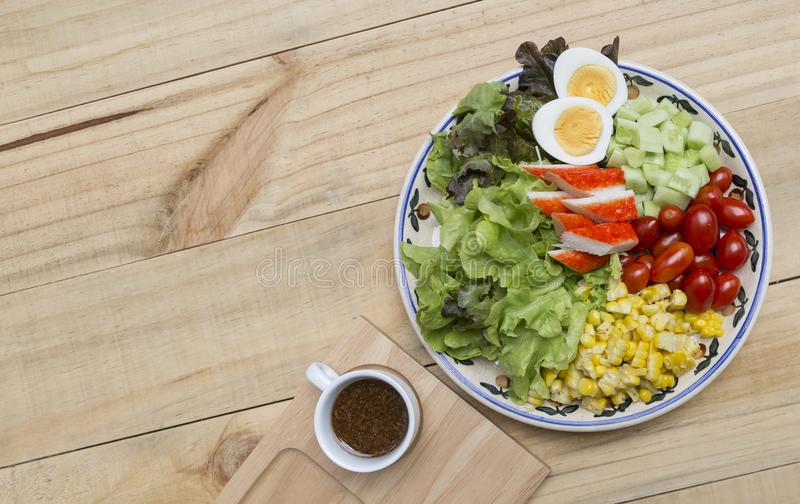 Healthy and diet food concept, fresh mixed vegetable with boil egg and crab stick salad with Japanese dressing stock image