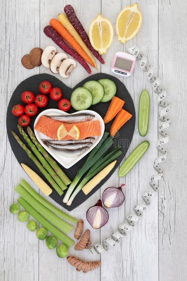 Healthy Diet Food. Health diet food concept with fresh fish, vegetables and fruit on heart shaped slate board on rustic background with pedometer and calorie royalty free stock images