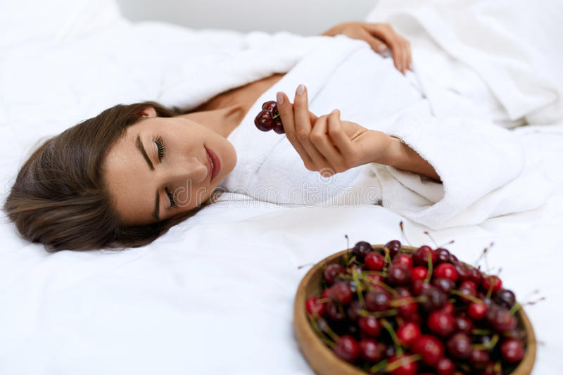 Healthy Diet Food For Woman's Health. Girl Eating Fruits On Bed. Healthy Diet Food For Woman's Health. Closeup Portrait Of Beautiful Happy Woman Eating Organic stock images