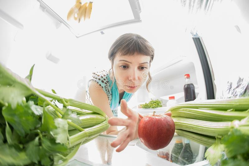 Healthy diet: A hand grabbing an apple from the open refrigerator full of greens. royalty free stock images