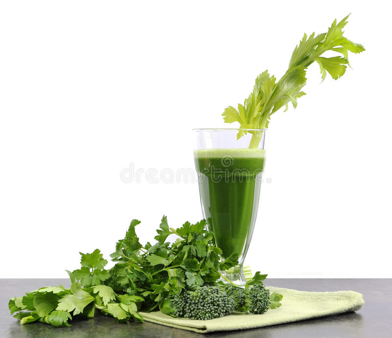 Healthy diet health foods with nutritious freshly juiced green vegetable juice. With celery, broccoli and parsley on black kitchen bench top against a white royalty free stock photography