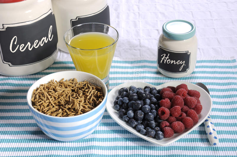 Healthy diet high dietary fiber breakfast. With bowl of bran cereal and berries on white heart plate on aqua blue with pineapple juice and jars stock photo
