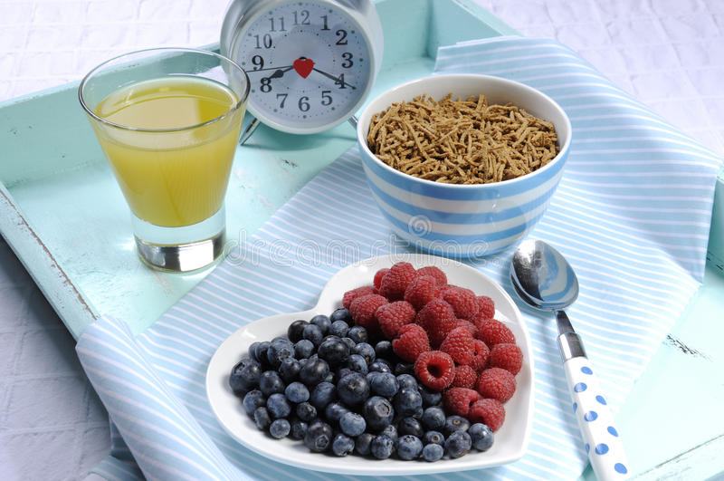 Healthy diet high dietary fiber breakfast on vintage tray. Healthy diet high dietary fiber breakfast with bowl of bran cereal and berries on white heart plate on royalty free stock photos