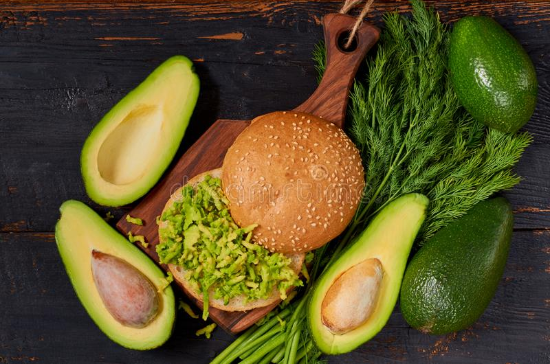 Healthy diet Mexican guacamole burger on the wooden board decorated with fresh herbs. Vegetarian green avocado sandwich royalty free stock images