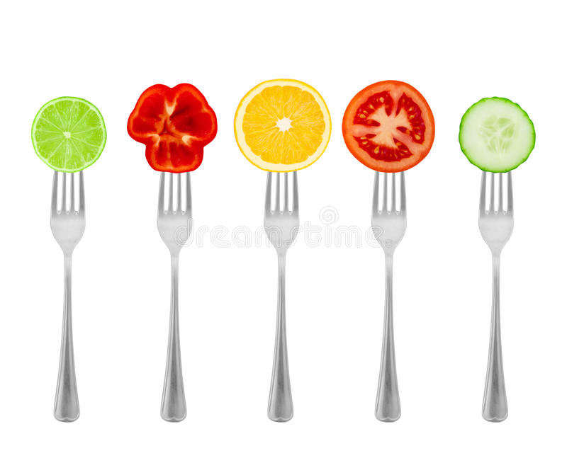 Healthy diet, organic food on forks with vegetables and fruit. stock image