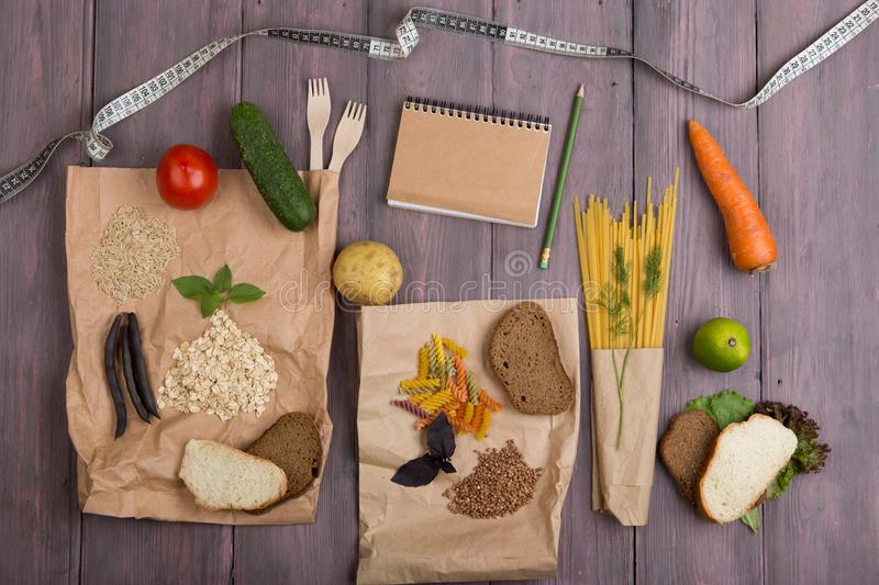 Healthy diet plan concept - Blank notebook for recipe, measure tape, eco bags with products rich of complex carbohedrates: cereals stock photo