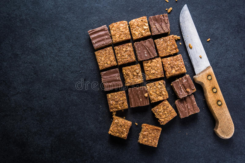 Healthy diet snack, oat flap jack brownie bar. View from overhead on dark slate stock photo