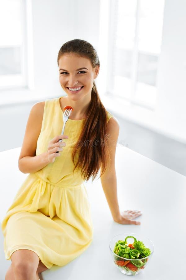 Healthy Diet. Woman Eating Vegetarian Salad. Healthy Eating, Foo. Healthy Diet. Beautiful Smiling Woman Eating Fresh Organic Vegetarian Salad In Modern Kitchen stock photo