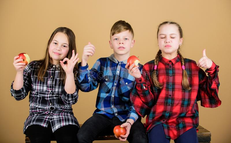 Healthy dieting and vitamin nutrition. Boy and girls friends eat apple snack while relaxing. School snack concept. Teens stock photography