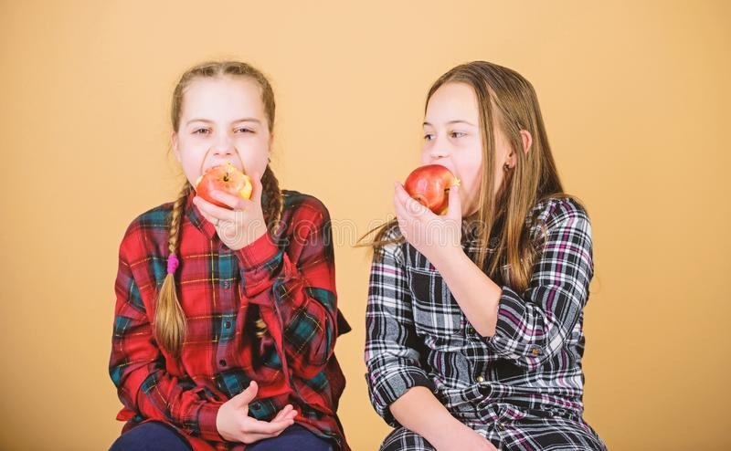 Healthy dieting and vitamin nutrition. Girls friends eat apple snack while relaxing. School snack concept. Teens with stock photos
