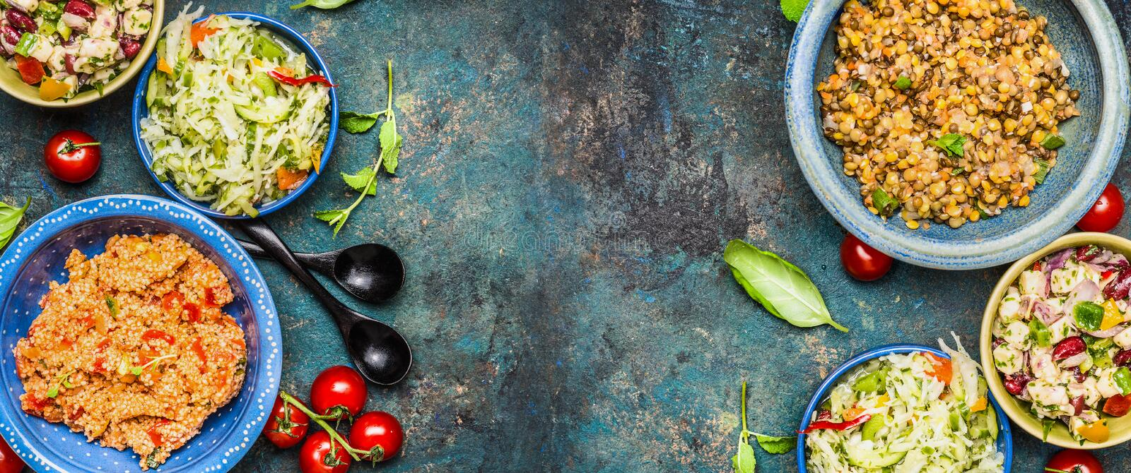 Healthy different salad bowls on dark vintage background. Country salads in rustic bowls. Salad bar, top view, banner. stock image