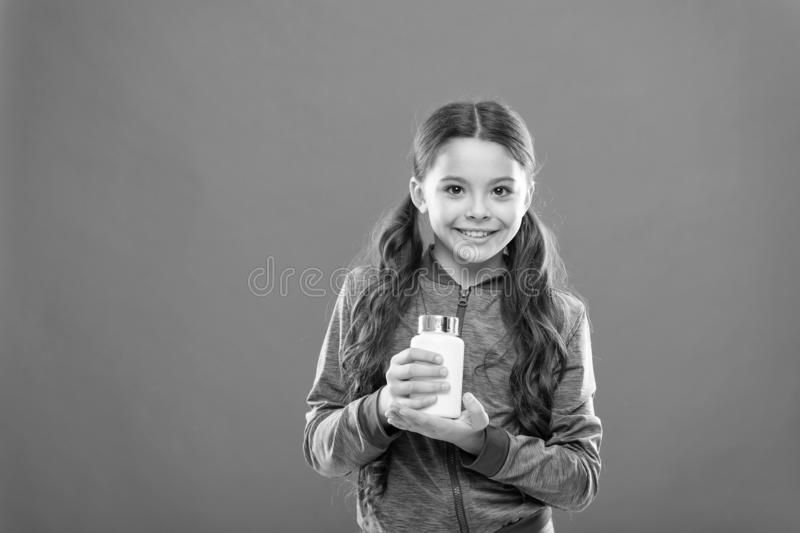 For healthy digestive flora. Dietary supplement for children. Take vitamin supplements. Girl hold medicines bottle. Vitamin and medicine concept. Child girl stock image