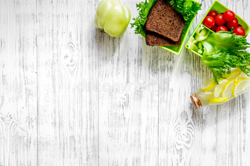 Healthy dinner in office. Lunch box with bread, tomato, salad and cheese on light wooden background top view copyspace stock photography