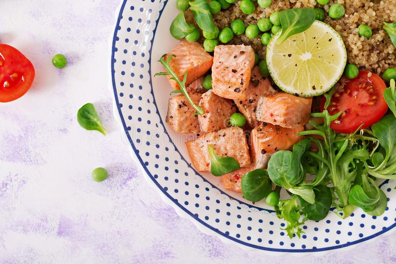 Healthy dinner. Slices of grilled salmon, quinoa, green peas, tomato, lime and lettuce leaves. royalty free stock photo
