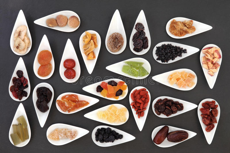 Healthy Dried Fruit. Large dried fruit selection in white dishes over slate background royalty free stock image