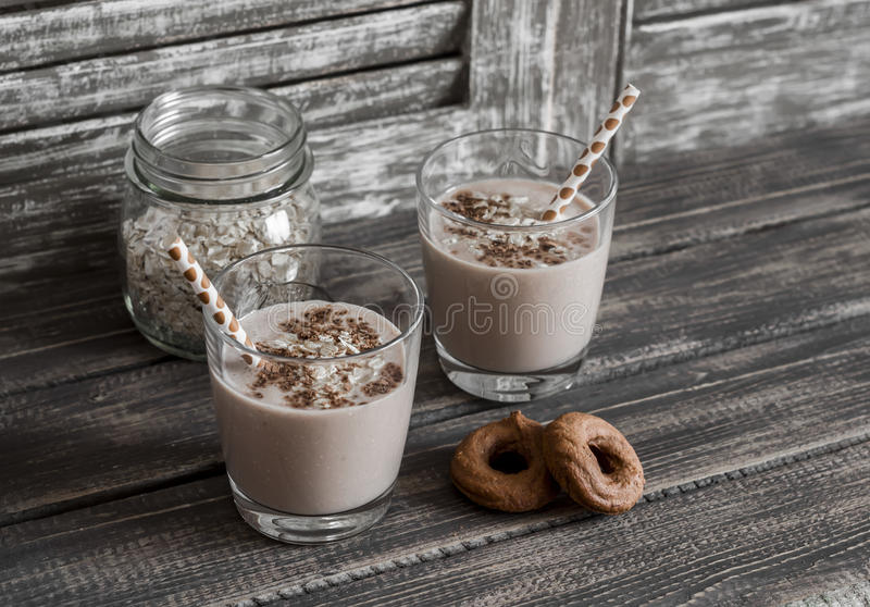 Healthy drink - banana and oatmeal smoothie in a glass on dark wooden background stock photos