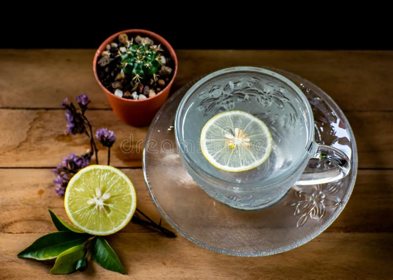 Healthy drink, cool lemon soda soft drinks served in beautiful crystal glass with small dish on wood table with sunshine morning. Warm Lemon soda,healthy drinks stock image