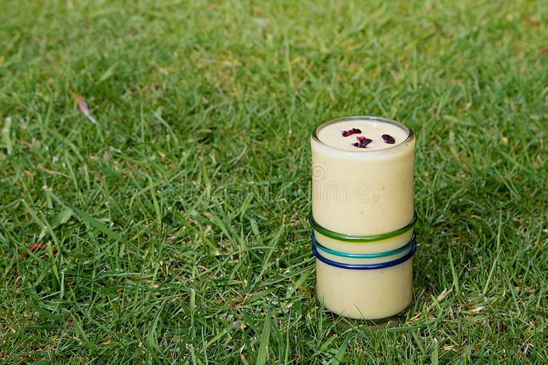 Healthy drink, yellow smoothie with red cranberries on top stock photo