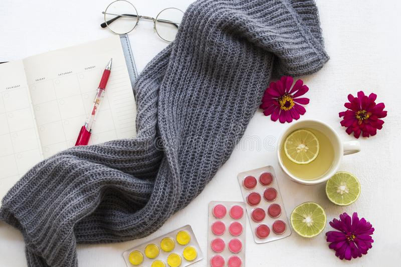 Healthy drinks hot honey lemon with knitting wool scarf. Herbal healthy drinks honey lemon with cough sore pills ,notebook and knitting wool scarf for lifestyle stock photo