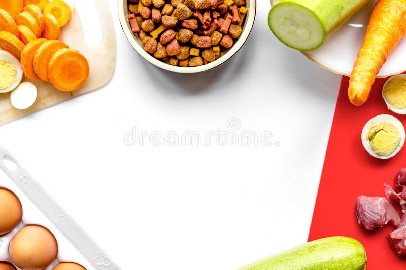 Healthy dry dogfood with ingredients on table top view mock up. Healthy dry dogfood with cut ingredients on kitchen table background top view mock up royalty free stock photo