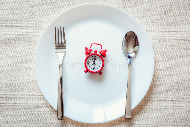 Healthy Eat Meal Time and Reminder Breakfast Concept, Food Timing Cycles for Eating, Red Alarm Clock With Stainless Steel Spoon royalty free stock photography