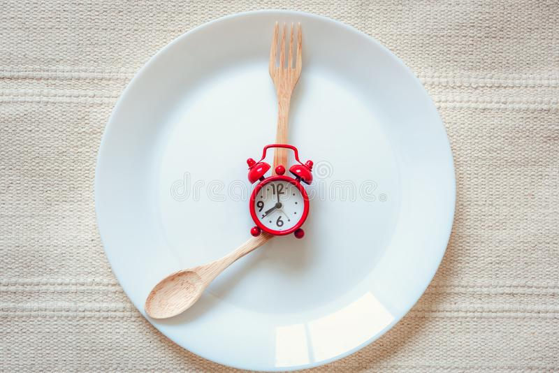 Healthy Eat Meal Time and Reminder Breakfast Concept, Food Timing Cycles for Eating, Red Alarm Clock With Wooden Spoon and Fork on. Ceramic Dish. Empty Plate stock photography
