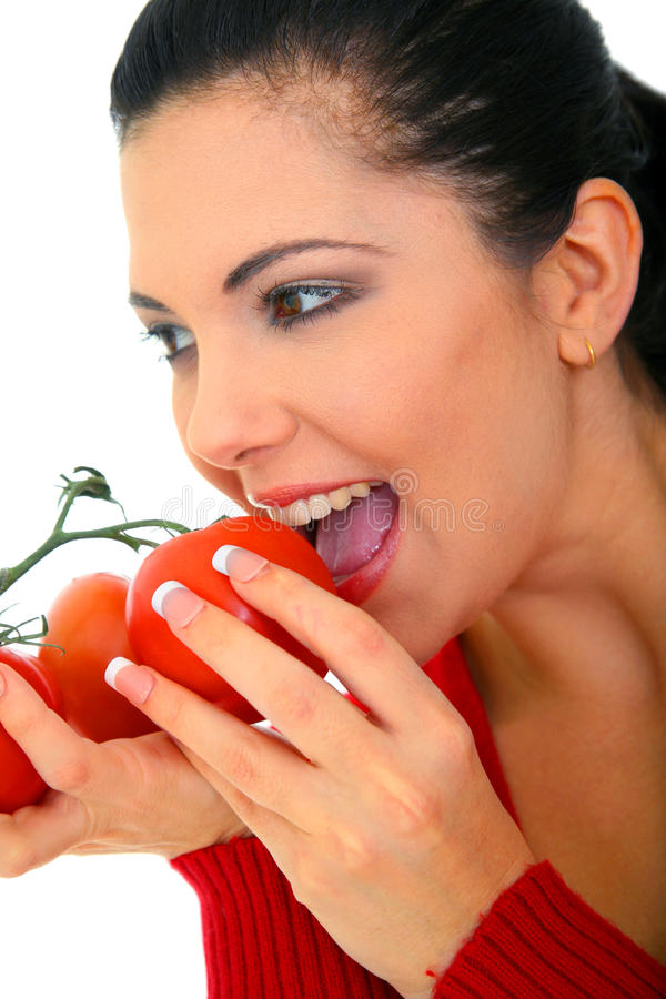 Healthy Eating. Young woman smiling eating fresh tomatoes. shallow depth of field royalty free stock photos